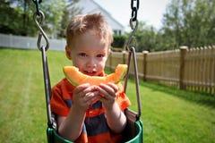 Garçon mangeant le melon Image libre de droits