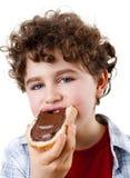 Garçon mangeant le sandwich avec de la crème de chococolate Photo libre de droits