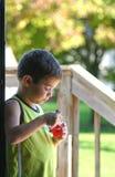 Garçon mangeant un casse-croûte Photographie stock libre de droits