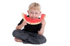 Garçon mangeant une pastèque sur l'étage Image libre de droits