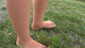 Garçon marchant nu-pieds sur l'herbe banque de vidéos