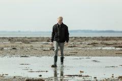 Garçon marchant par le grand magma près de la plage Photographie stock libre de droits