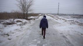 Garçon marchant sur la route congelée banque de vidéos