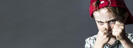 Garçon menaçant avec les taches de rousseur et le chapeau rouge semblant violents, bannière Photographie stock libre de droits