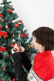 Garçon mettant l'ornement sur l'arbre de Noël Photo stock