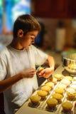 Garçon mettant le glaçage sur des petits gâteaux Photos stock