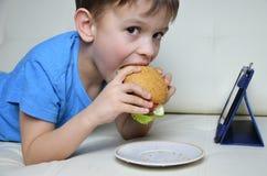 Garçon mignon à la maison sur le divan, mangeant un hamburger et regardant le comprimé, les bandes dessinées de observation ou pa Photo libre de droits