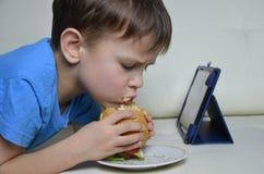 Garçon mignon à la maison sur le divan, mangeant un hamburger et regardant le comprimé, les bandes dessinées de observation ou pa Photo stock