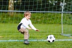 Garçon mignon adorable de petit enfant jouant le football et le football sur le champ Photo stock