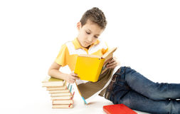 Garçon mignon affichant un livre sur l'étage Images stock