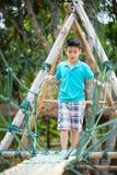 Garçon mignon asiatique heureux jouant sur le terrain de jeu Photo stock