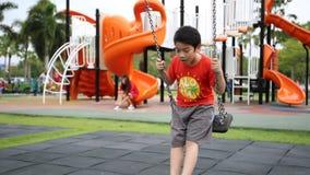 Garçon mignon asiatique jouant en parc banque de vidéos