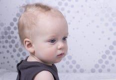 Garçon mignon aux yeux bleus triste et sérieux d'enfant en bas âge Image stock
