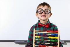 Garçon mignon avec l'abaque contre le tableau blanc dans la salle de classe Photo stock