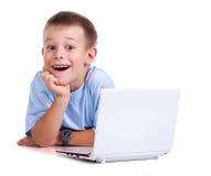 Garçon mignon avec l'ordinateur portatif sur le blanc photographie stock libre de droits