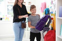Garçon mignon avec la mère choisissant le sac à dos photos libres de droits