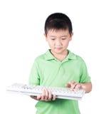 Garçon mignon avec le clavier d'isolement sur le fond blanc Photo stock