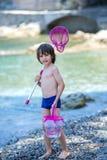 Garçon mignon avec le filet pour la pêche et le seau, essayant d'attraper un certain l Image libre de droits