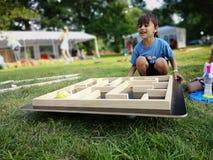 Garçon mignon avec le jeu en bois de labyrinthe de boule en parc photo stock