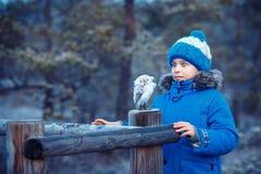 Garçon mignon avec le jouet de hibou sur l'épaule dans la forêt d'hiver Photos stock