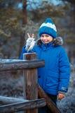 Garçon mignon avec le jouet de hibou sur l'épaule dans la forêt d'hiver Photo stock