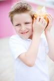 Garçon mignon avec le seashell photos stock