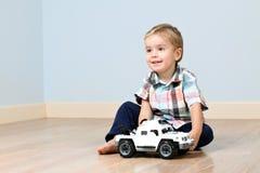 Garçon mignon avec le véhicule de jouet photographie stock libre de droits