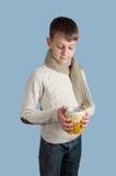 Garçon mignon avec une tasse blanche sur le fond bleu Image stock