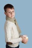 Garçon mignon avec une tasse blanche sur le fond bleu Image libre de droits