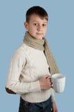 Garçon mignon avec une tasse sur le fond bleu Photos stock