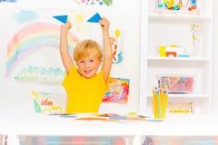 Garçon mignon blond apprenant des formes tenant des triangles Image stock