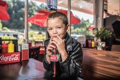 Garçon mignon buvant d'un coca-cola dans une veste en cuir photos stock