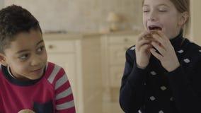 Garçon mignon d'afro-américain et fille caucasienne blonde avec des yeux bleus jouant dans la cuisine Peu combat heureux d'amis banque de vidéos