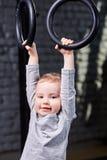 Garçon mignon d'enfant accrochant sur les anneaux gymnastiques dans le gymnase convenable de croix contre le mur de briques Image stock