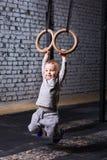 Garçon mignon d'enfant accrochant sur les anneaux gymnastiques dans le gymnase convenable de croix contre le mur de briques Photos stock