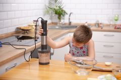 Garçon mignon d'enfant en bas âge à l'aide du mélangeur de main pour faire la viande hachée Préparation du repas dans la cuisine images libres de droits