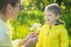 Garçon mignon d'enfant en bas âge faisant a avec avant souffler les pissenlits secs Photographie stock libre de droits
