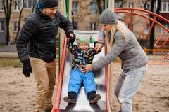 Garçon mignon d'enfant en bas âge jouant avec le père et la mère sur le terrain de jeu Photographie stock