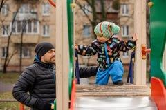 Garçon mignon d'enfant en bas âge jouant avec le père sur le terrain de jeu Photo libre de droits