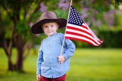 Garçon mignon d'enfant en bas âge tenant le drapeau américain en beau parc Image libre de droits