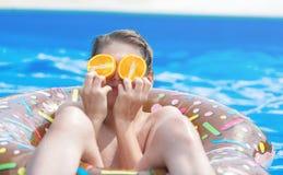 Garçon mignon d'enfant sur l'anneau gonflable drôle de flotteur de beignet dans la piscine avec des oranges Adolescent apprenant  photographie stock