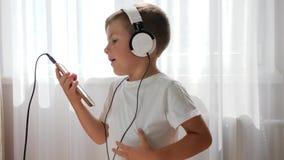 Garçon mignon dans des écouteurs avec le téléphone dans des mains écoutant la musique et la danse banque de vidéos