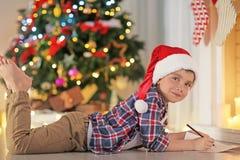 Garçon mignon dans la lettre d'écriture de chapeau de Noël à Santa à la maison Photos stock