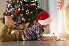 Garçon mignon dans la lettre d'écriture de chapeau de Noël à Santa à la maison Photo stock