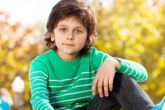 Garçon mignon dans le chandail vert avec le bras sur son genou Photo libre de droits