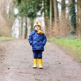 Garçon mignon de petit enfant marchant par la forêt d'automne Images stock