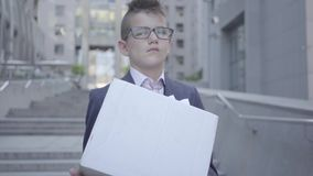 Garçon mignon de portrait petit en costume et verres tenant une boîte avec la papeterie sur les escaliers dehors Enfant As clips vidéos