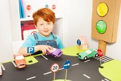 Garçon mignon de roux jouant le conducteur dans le jardin d'enfants Images libres de droits