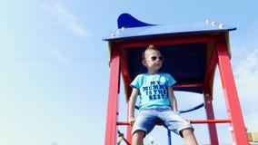 Garçon mignon de sept ans ayant l'amusement sur un terrain de jeu dehors en été Mouvement lent Enfance actif joyeux clips vidéos