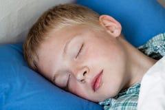 Garçon mignon dormant dans le lit photos libres de droits